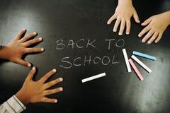 Mains d'enfants de Multiraces sur le tableau noir Images stock