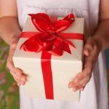 Mains d'enfants jugeant un cadeau en gros plan Photographie stock