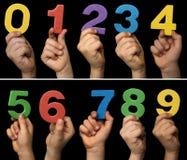 Mains d'enfants retenant des numéros Photos libres de droits