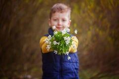 Mains d'enfants tenant des fleurs de ressort de bouquet WI de foyer en main Image libre de droits