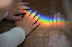 Mains d'enfants touchant l'arc-en-ciel photos stock