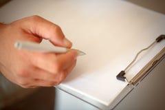 Mains d'homme d'affaires avec l'écriture de stylo sur le papier dans la fin  Images stock