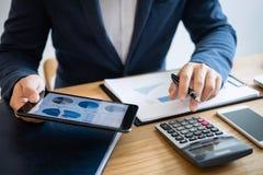 Mains d'homme d'affaires utilisant l'information des textes sur le comprimé numérique à l' photo stock