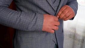 Mains d'homme boutonnant la fin de veste  L'homme ?l?gant dans une attache de costume se boutonne sur sa veste banque de vidéos
