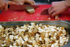 Mains d'homme coupant le pain pour des croûtons sur le doard de coupure rouge image stock