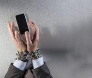 Mains d'homme d'affaires attachées par chaîne saisissant le téléphone de communication corporate images stock