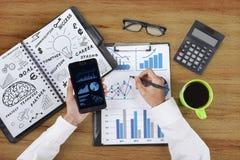 Mains d'homme d'affaires fonctionnant avec le smartphone Image stock