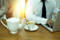 Mains d'homme d'affaires utilisant le carnet avec la tasse du thé et du citron sur l'OE Photo libre de droits