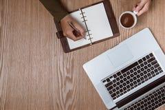 Mains d'homme d'affaires utilisant un ordinateur portable avec une tasse de café et futé Image stock