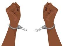 Mains d'homme d'afro-américain cassant des menottes d'acier Image libre de droits