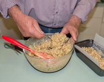 Mains d'homme d'une cinquantaine d'années administrant le mélange à la cuillère de gâteau Image stock