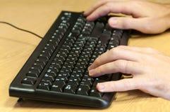 Mains d'homme dactylographiant sur un clavier Photo stock