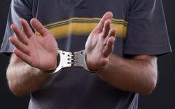 Mains d'homme dans des menottes Photo libre de droits