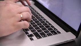 Mains d'homme dans le type à carreaux de chemise sur le clavier noir du carnet gris clips vidéos