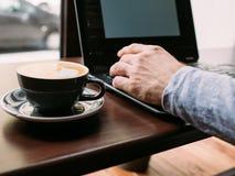 Mains d'homme de travail de pause-café dactylographiant la tasse d'ordinateur portable photos stock