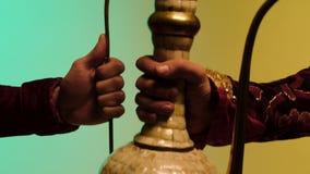 Mains d'homme donnant la cruche en céramique orientale sur le fond bleu et jaune, marchandises antiques vendant le concept barre  banque de vidéos