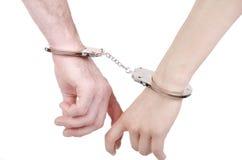 Mains d'homme et de femme dans des menottes. Images stock
