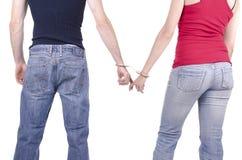 Mains d'homme et de femme dans des menottes. Photographie stock