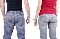 Mains d'homme et de femme dans des menottes Photos stock