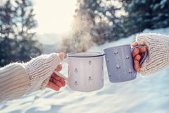 Mains d'homme et de femme dans des mitaines de tricotage avec des tasses de thé chaud dessus Photos libres de droits