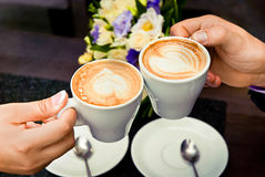 Mains d'homme et de femme et tasses de café Image stock