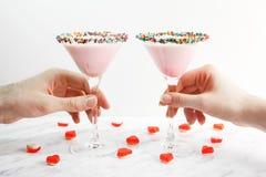Mains d'homme et de femme prenant le cocktail rose de lait, plan rapproché Décoré des coeurs de gelée Jour du ` s de Valentine de Images libres de droits
