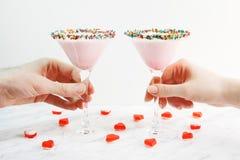 Mains d'homme et de femme prenant le cocktail rose de lait, plan rapproché Décoré des coeurs de gelée Jour du ` s de Valentine de Photo stock