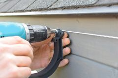 Mains d'homme installant le support de gouttière de toit image stock