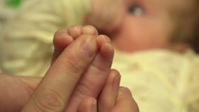 Mains d'homme massant de petits pieds nouveau-nés de bébé closeup 4K UltraHD, UHD banque de vidéos