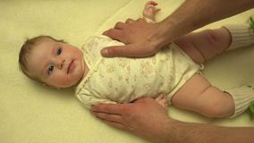 Mains d'homme massant le corps nouveau-né de bébé closeup 4K UltraHD, UHD banque de vidéos