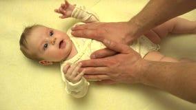 Mains d'homme massant le corps nouveau-né de bébé closeup 4K UltraHD, UHD clips vidéos