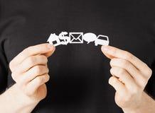 Mains d'homme montrant les symboles de papier Image stock