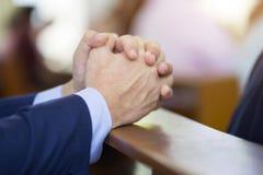 Mains d'homme priant sur une Sainte Bible dans l'église pour le concept de foi, la spiritualité et la religion chrétienne images stock