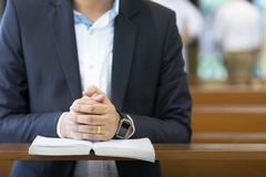 Mains d'homme priant sur une Sainte Bible dans l'église pour le concept de foi, la spiritualité et la religion chrétienne photo stock