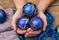Mains d'homme tenant des boules de Noël Photos stock