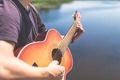 Mains d'homme tenant la guitare acoustique en nature Concepts de musique et d'été photos stock