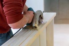 Mains d'homme tenant la scie circulaire et préparant pour faire une porte en bois coupée images libres de droits