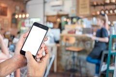 Mains d'homme tenant le téléphone intelligent Image stock