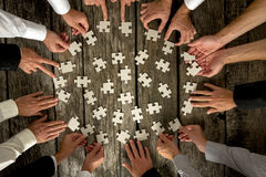 Mains d'hommes d'affaires tenant des morceaux de puzzle sur le Tableau Photos stock