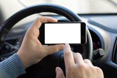 Mains d'hommes tenant le téléphone avec l'écran conduisant dans la voiture Photos stock