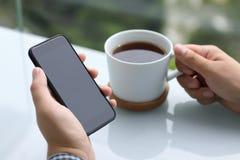 Mains d'hommes tenant le téléphone avec le thé noir d'écran et de tasse Photographie stock libre de droits