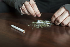 Mains d'intoxiqué faisant le plan rapproché de jambage de marijuana photo libre de droits
