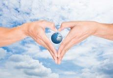 Mains d'isolement de forme de coeur et le monde Images libres de droits