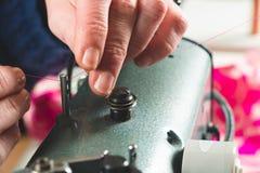 Mains d'ouvrière couturière plaçant le fil dans la machine à coudre Photo stock