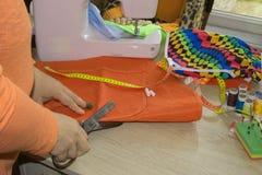 Mains d'ouvrière couturière sur la table de travail avec la bande de mesure Tailleur h Photographie stock