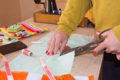 Mains d'ouvrière couturière sur la table de travail avec la bande de mesure Travaillez les mains fonctionnant avec le tissu de te Image libre de droits