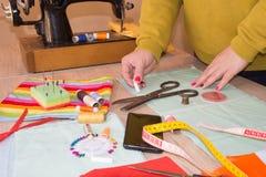 Mains d'ouvrière couturière sur la table de travail avec la bande de mesure Travaillez les mains fonctionnant avec le tissu de te Photographie stock libre de droits