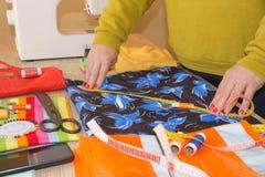 Mains d'ouvrière couturière sur la table de travail avec le modèle et la bande de mesure Un tailleur présente une robe Photo libre de droits