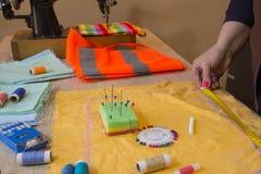 Mains d'ouvrière couturière sur la table de travail avec le modèle et la bande de mesure Un tailleur présente une robe Photos libres de droits