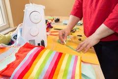 Mains d'ouvrière couturière sur la table de travail avec le modèle et la bande de mesure Un tailleur présente une robe Image libre de droits